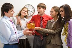 Portrait of friendly colleagues giving birthday present to happy man in office Stock Photos