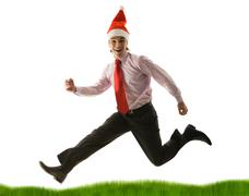 Portrait of businessman in santa cap running down green grass on white backgroun Stock Photos