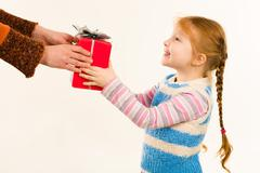 little girl taking christmas present from female hands over white background - stock photo