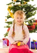 portrait of cute girl sitting with decorated fir tree behind and looking at came - stock photo