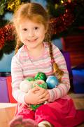 Portrait of cute child sitting with pile of decorative balls in hands Stock Photos