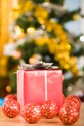 Image of red giftbox surrounded by several toy balls on glittering background Stock Photos