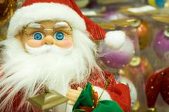 photo of toy santa claus wearing eyeglasses and red fur cap in shopping mall - stock photo