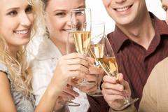 Photo of happy friends holding glasses full of champagne and smiling during part Kuvituskuvat