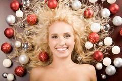 Creative image of smiling blond girl with lots of decorative balls on ends of he Stock Photos