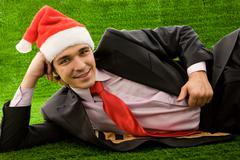 Stock Photo of young man relaxing on green grass and looking at camera with smile
