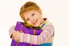 Portrait of cute child with big violet giftbox smiling and looking at camera Stock Photos