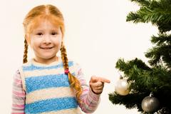 Portrait of funny girl pointing at one of decorative toy balls on fir tree branc Stock Photos