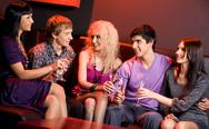 Stock Photo of portrait of smart friends with flutes in hands communicating at party