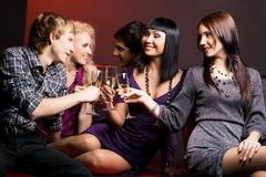 portrait of joyful friends toasting with flutes of champagne at party - stock photo