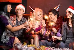 Portrait of happy guys and girls enjoying new year party with champagne and beng Stock Photos