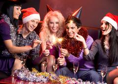 photo of cheerful friends laughing and having fun at christmas party - stock photo
