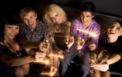 View from above of joyful friends with champagne and sparkling lights in hands d Stock Photos