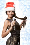 portrait of beautiful female wearing santa cap and holding champagne - stock photo