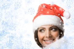 Face of smiling woman in santa cap looking out of snowflakes Stock Photos