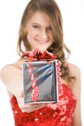 Close-up of christmas present in female's hand being given by smart girl Stock Photos
