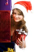 portrait of beautiful girl holding present behind pile of boxes - stock photo