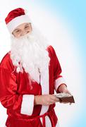 Portrait of cheerful santa holding wallet in hands and looking at camera Stock Photos