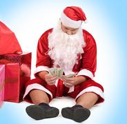 portrait of serious santa counting his wage - stock photo