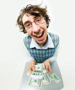 fish-eye shot of happy young man holding several packs of dollars and smiling - stock photo