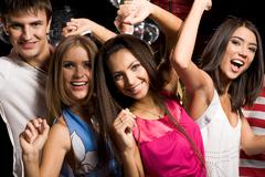 Portrait of four clubbing friends looking at camera with smiles while dancing Stock Photos