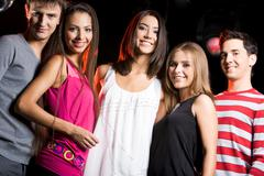 portrait of smart teens standing in line and looking at camera with smiles - stock photo