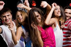 company of cheerful teens enjoying themselves while dancing at disco - stock photo