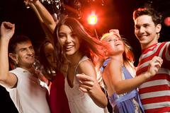 Beautiful girl making gesture meaning to join her dancing friends at party Stock Photos