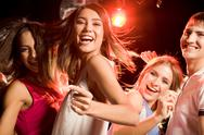Stock Photo of pretty clubber dancing surrounded by her friends and looking at camera with smil