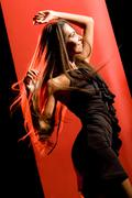 portrait of beautiful dancer wearing elegant black dress and moving over red bac - stock photo
