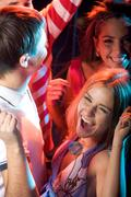 Joyful girl raising her hands during dance with friends near by Stock Photos