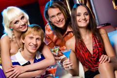 portrait of happy friends gathered together in night club to have a party - stock photo