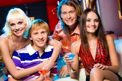 portrait of friendly young people looking at camera with smiles in the bar - stock photo