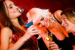 Two happy girls chatting and drinking spirits with smiling guy during party Stock Photos