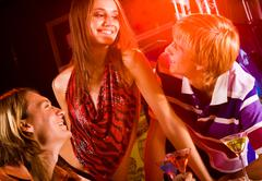 Portrait of happy friends talking and laughing at party in the bar Stock Photos
