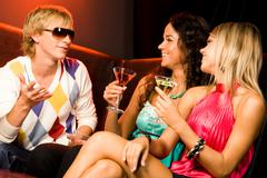 portrait of handsome man speaking something to pretty women at party - stock photo