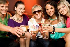 Stock Photo of portrait of young people touching the glasses with each other in the nightclub