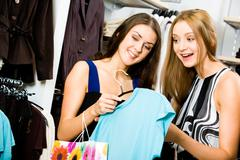 Portrait of young girls in the department store holding fashionable t-shirt and Stock Photos