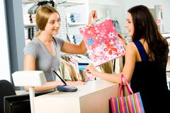 portrait of shop assistant giving shopping bag to happy woman in the shopping ma - stock photo
