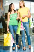 image of two attractive women holding the bags and standing in the shopping mall - stock photo