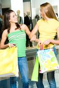 portrait of two women having a conversation in the shopping mall - stock photo