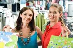 portrait of cheerful girls carrying shopping bags and looking at camera happily - stock photo