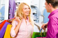 Portrait of happy blond woman looking at smiling man and holding bags in hands Stock Photos