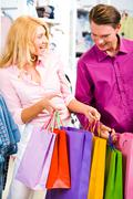 portrait of cheerful woman showing presents to her boyfriend in the store - stock photo