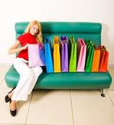 image of elegant lady sitting on sofa with row of bags on it and looking into on - stock photo