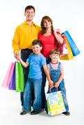 Portrait of happy family standing and holding bags while looking at camera with Stock Photos