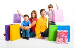 image of happy parents and their two sons sitting in studio with shopping bags n - stock photo