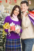 Portrait of happy young couple with christmas gifts looking somewhere in shoppin Stock Photos