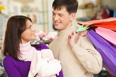 photo of handsome man looking at his wife during shopping in trade center - stock photo