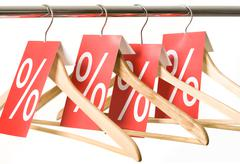 Photo of hangers with red labels showing holiday discount and sale Stock Photos